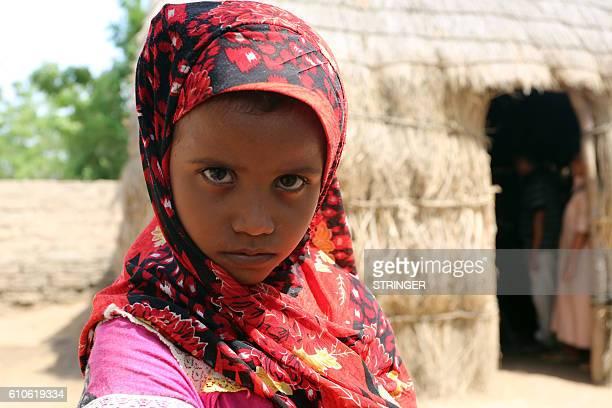 A Yemeni girl stands outside a house on September 26 2016 in an impoverished coastal village on the outskirts of the rebelheld Yemeni port city city...