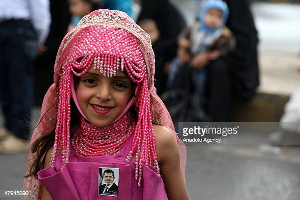 Yemeni girl wearing a pin picturing Mohamed Morsi takes part in a demonstration to mark the third anniversary of the Friday of Dignity massacre on...