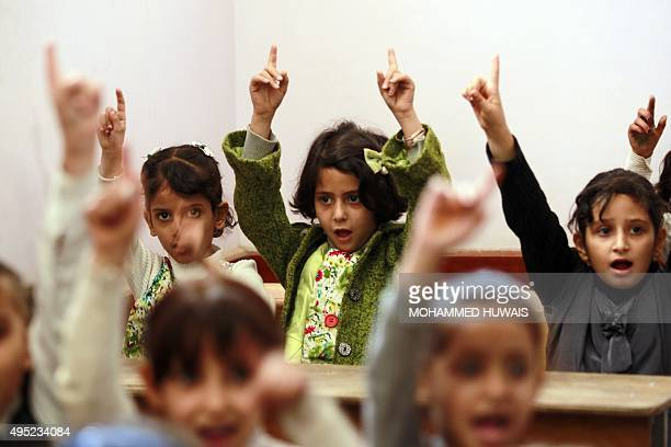 Yemeni girls raise their fingers on their fist day of school at a public institution in the Yemeni capital Sanaa on November 1 2015 AFP PHOTO /...