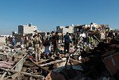 Yemeni Huthi rebels and members of the security forces loyal to the Shiite movement inspect the damage at the scene of a Saudi air strike targeting...