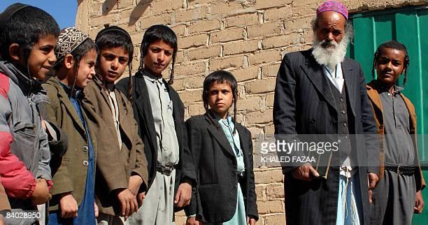 Yemeni Jewish boys walk with their teacher Imran Said alJaradi outside the Shabazi Hebrew school in the village of Raydah in Amran province 70...
