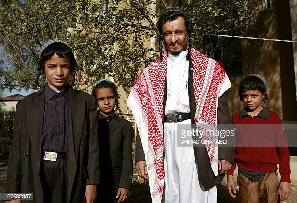 Yemeni Jewish Rabbi Yahia Yussef Mussa sporting a chequerred Keffiya poses for a picture with unidentified young relatives outside his apartment in...
