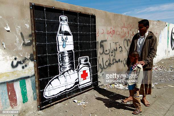 A Yemeni man and child look at a piece of art by Yemeni artist Murad Zubei depicting the blockade in Yemen and the prevention of the entry of food...