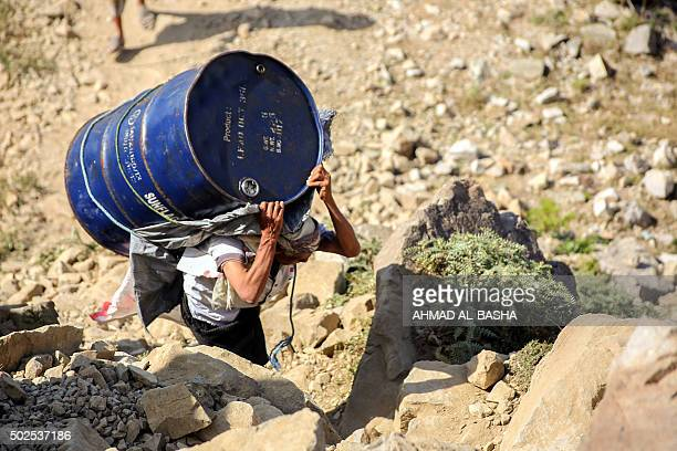 A Yemeni man carries a barrel of supplies as he walks through the mountains along the only path accessible between the southern cities of Aden and...