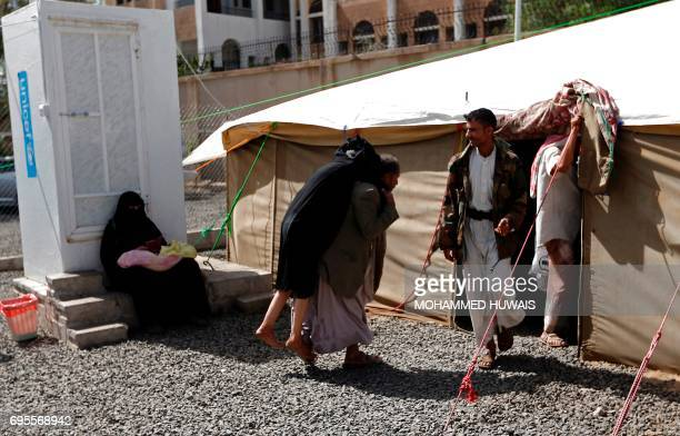 A Yemeni man carries a woman suspected of being infected with cholera as they arrive for treatment at Sabaeen Hospital in Sanaa on June 13 2017 Six...