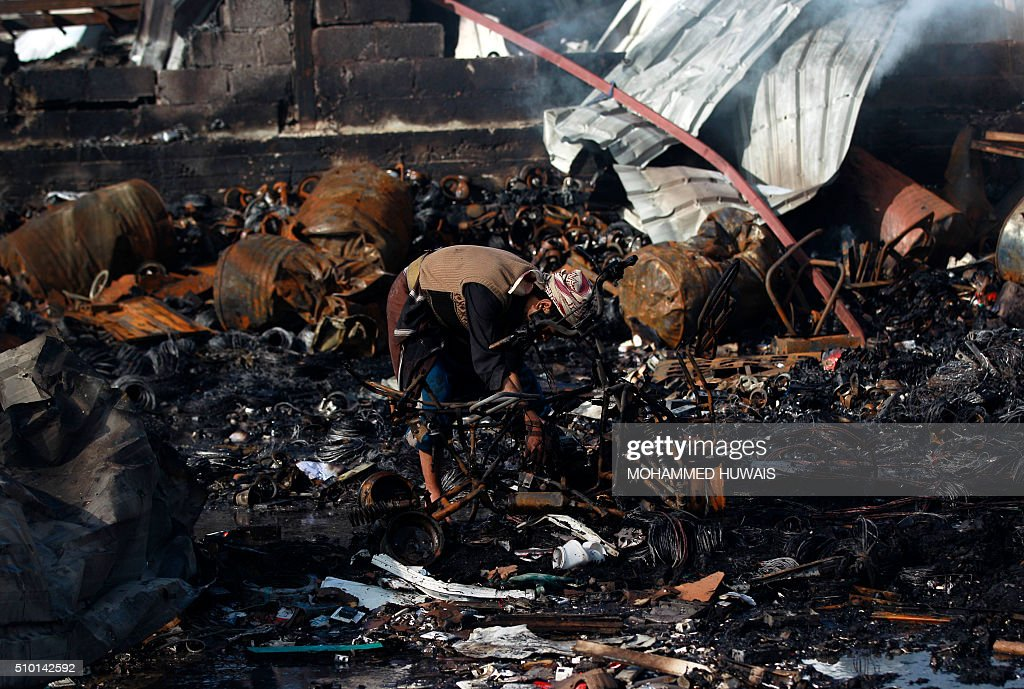 A Yemeni man inspects the damage at the site of a Saudi-led coalition air strike which hit a sewing workshop, in the capital Sanaa, on February 14, 2016. The factory owner, Faisal al-Musaabi, told AFP that 'Two employees, including a 14-year-old boy, were killed and 15 others wounded in the overnight air raid,'. The coalition has been carrying out air strikes against Iran-backed rebels across Yemen since March. HUWAIS