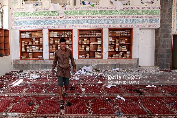 A Yemeni man inspects the damage following a bomb explosion at the Badr mosque in southern Sanaa on March 20 2015 Triple suicide bombings killed at...