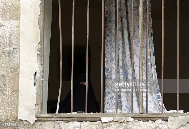 A Yemeni man looks on from behind the bars of her damaged window next to the Kobbat alMehdi Shiite mosque in the capital Sanaa on June 20 after a car...