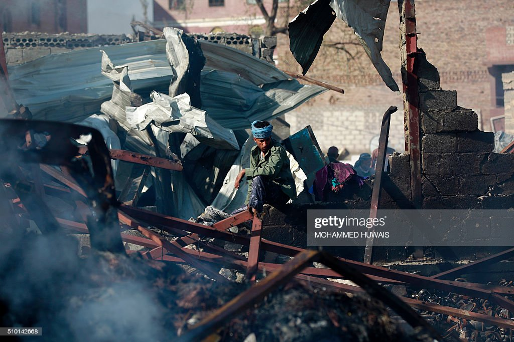 A Yemeni man sits amid the debris at the site of a Saudi-led coalition air strike which hit a sewing workshop, in the capital Sanaa, on February 14, 2016. The factory owner, Faisal al-Musaabi, told AFP that 'Two employees, including a 14-year-old boy, were killed and 15 others wounded in the overnight air raid,'. The coalition has been carrying out air strikes against Iran-backed rebels across Yemen since March. HUWAIS