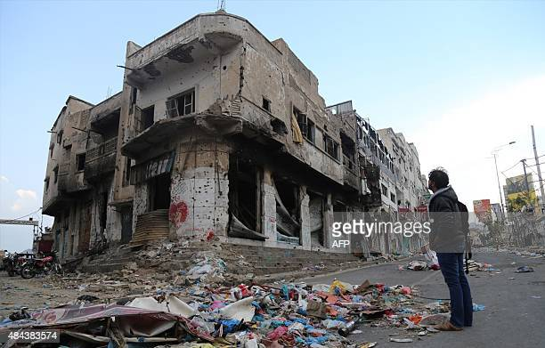 A Yemeni man stands near a building heavily damaged by fighting between government loyalists and rebels in Yemen's third city Taez on August 17 2015...