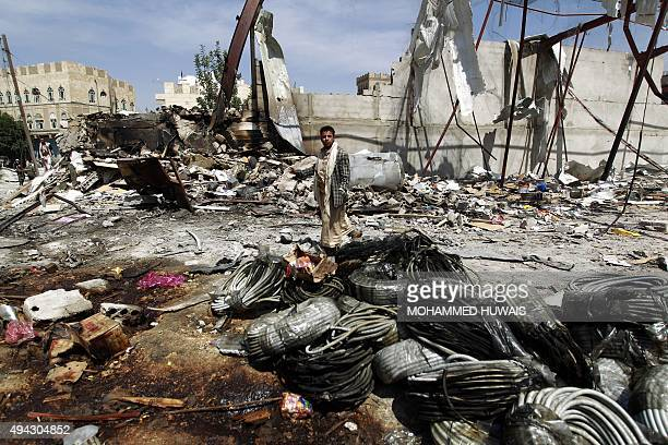 A Yemeni man walks amid the rubble of a food storage warehouse after it was targeted by air strikes carried out by the Saudiled coalition in the...