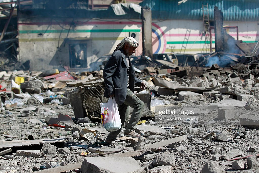 A Yemeni man walks amid the ruins of a school and a bowling club hit by an air-strike carried out by the Saudi-led coalition, in the capital Sanaa, on February 12, 2016. / AFP / MOHAMMED HUWAIS