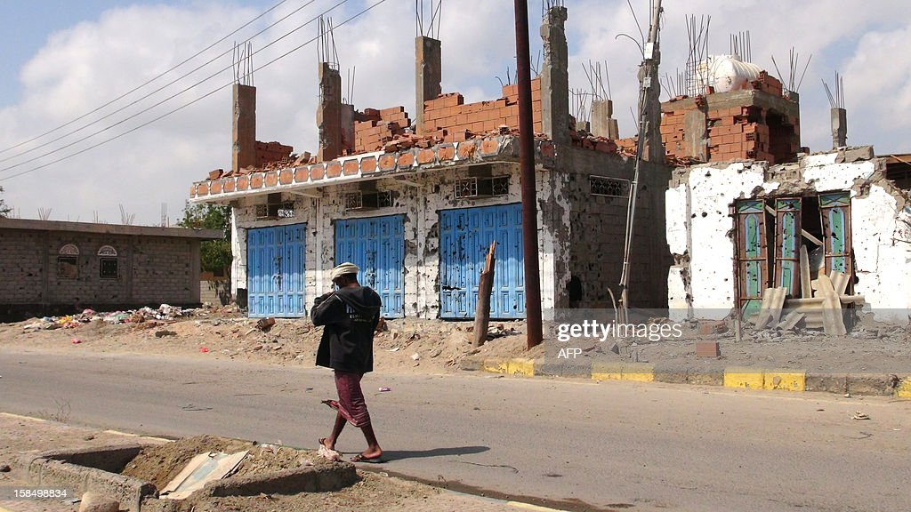 A Yemeni man walks past destroyed buildings in Zinjibar, capital of Abyan province in southern Yemen on December 5, 2012, six months after the Yemeni army ousted al-Qaeda loyalists from the region. Before a counter-offensive by the army earlier this year, Al-Qaeda held large swathes of southern Yemen. But since its loss of a string of towns near the port city of Aden in June, most have fled into desert regions farther east. Although weakened, they continue to launch hit-and-run attacks on government and civilian targets across Yemen. AFP PHOTO/SAMI AL-ANSI