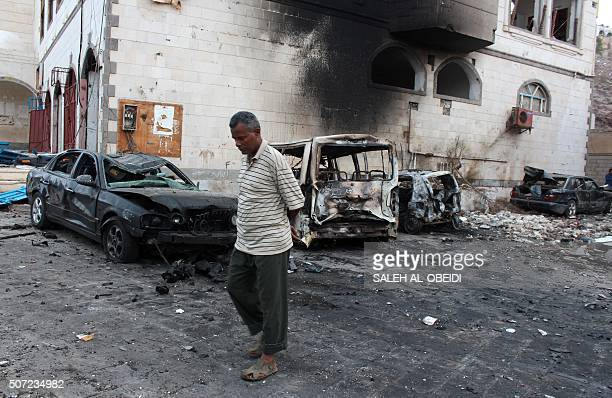 A Yemeni man walks past the site of a suicide car bombing outside Yemen's presidential palace in the city of Aden on January 28 2016 Islamic State...