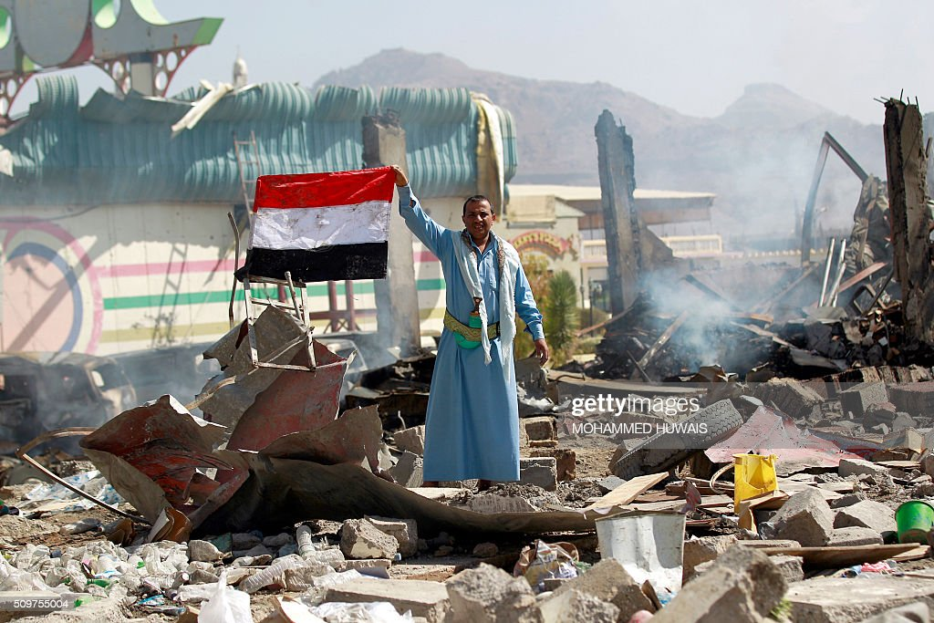 A Yemeni man waves his national flag as he stands amid the ruins of a school and a bowling club hit by an air-strike carried out by the Saudi-led coalition, in the capital Sanaa, on February 12, 2016. / AFP / MOHAMMED HUWAIS