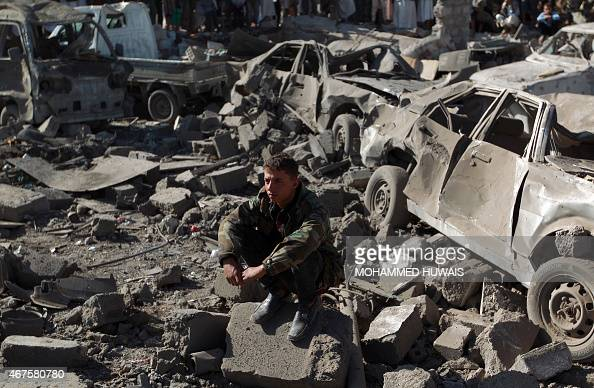 A Yemeni man wearing a military fatigue sits above debris at the site of a Saudi air strike against Huthi rebels near Sanaa Airport on March 26 which...