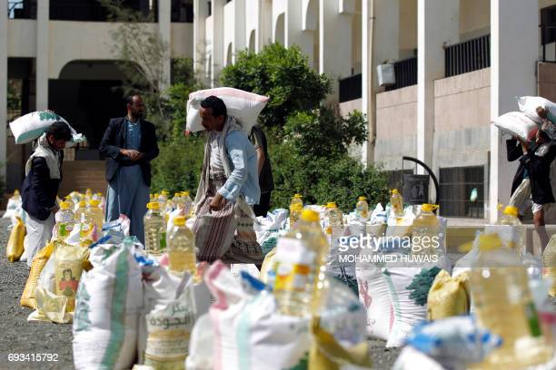 Yemeni men carry food aid distributed by a local charity during the Muslim holy fasting month of Ramadan in the capital Sanaa on June 7 2017 / AFP...