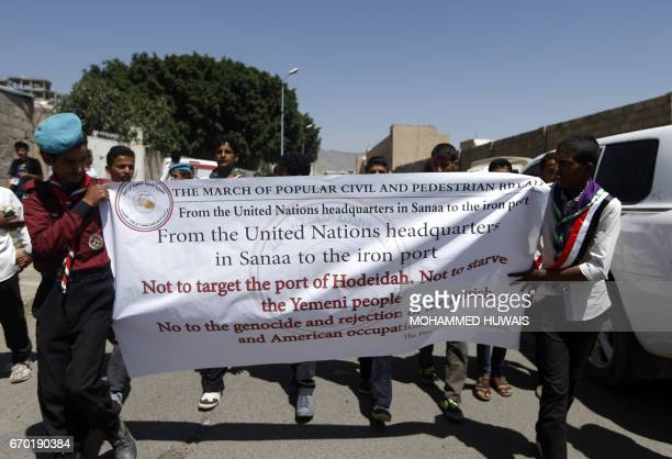 Yemeni men hold a banner during a 'protest for bread' march from the capital Sanaa to the coastal town of Hodeida on April 19 demanding an end to the...
