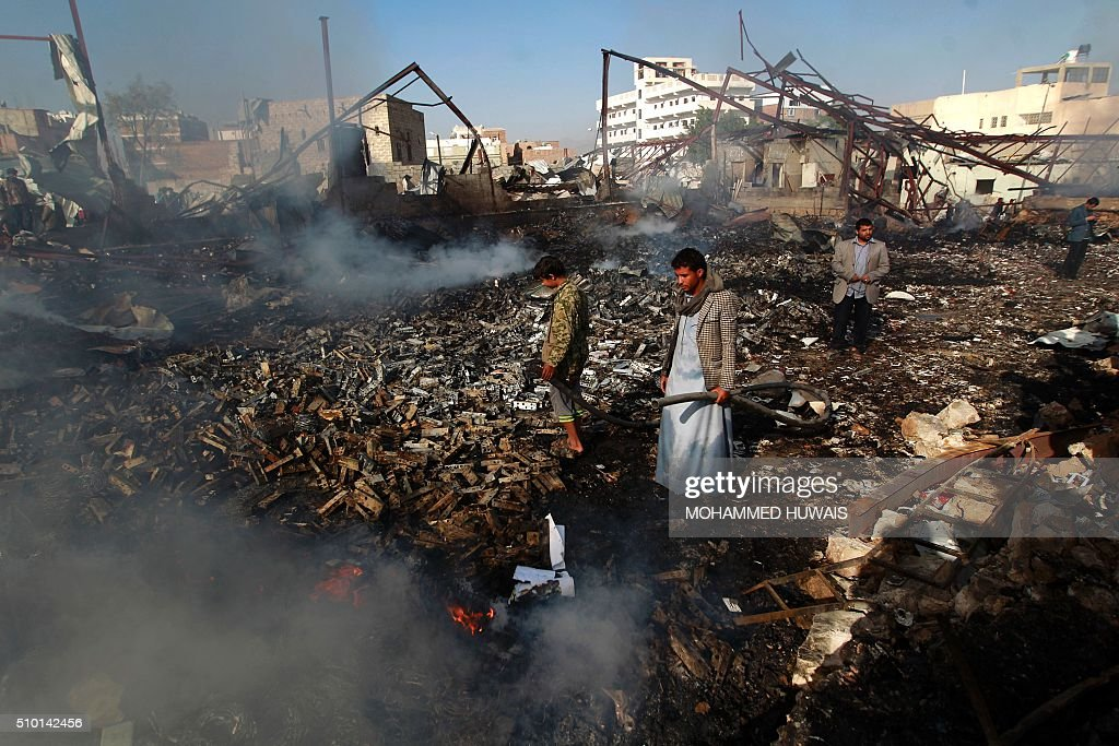 Yemeni men inspect the damage at the site of a Saudi-led coalition air strike which hit a sewing workshop, in the capital Sanaa, on February 14, 2016. The factory owner, Faisal al-Musaabi, told AFP that 'Two employees, including a 14-year-old boy, were killed and 15 others wounded in the overnight air raid,'. The coalition has been carrying out air strikes against Iran-backed rebels across Yemen since March. HUWAIS