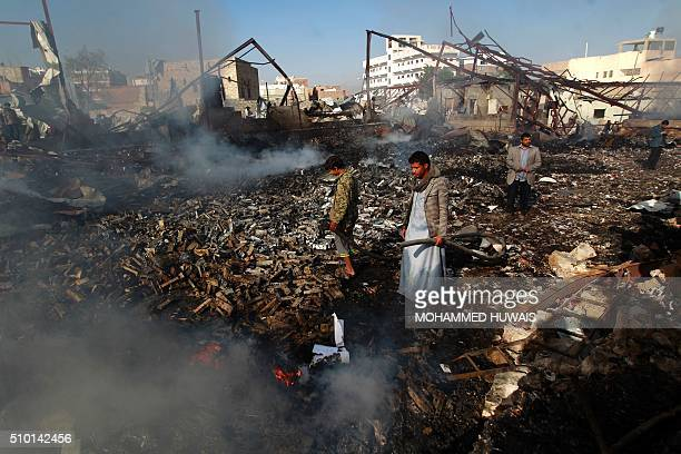 Yemeni men inspect the damage at the site of a Saudiled coalition air strike which hit a sewing workshop in the capital Sanaa on February 14 2016 The...