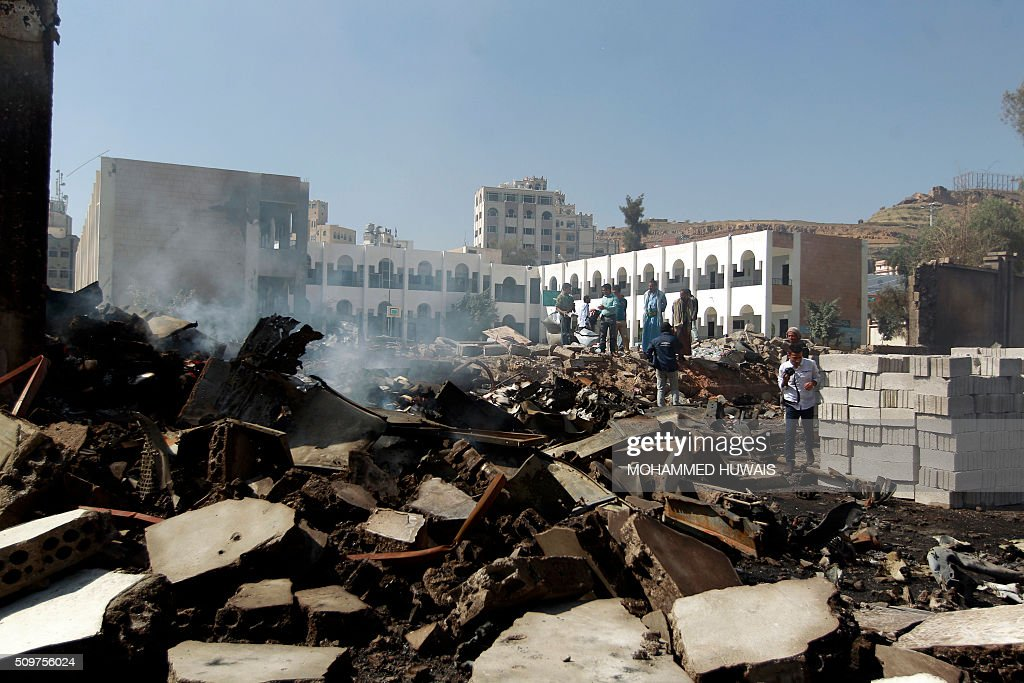 Yemeni men inspects the damage following an air-strike carried out by the Saudi-led coalition on a school and a bowling club, in the capital Sanaa, on February 12, 2016. / AFP / MOHAMMED HUWAIS