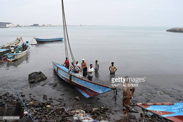 Yemeni men lift a damaged fishing boat out of the water following a tropical cyclone that has slammed into the warracked country on November 3 in the...