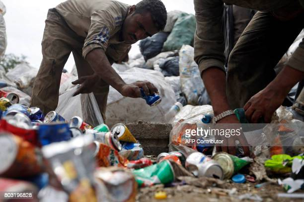 Yemeni men scavenge for recyclable items at a garbage dump on the outskirts of Sanaa on June 29 2017 Cholera a highly contagious bacterial infection...