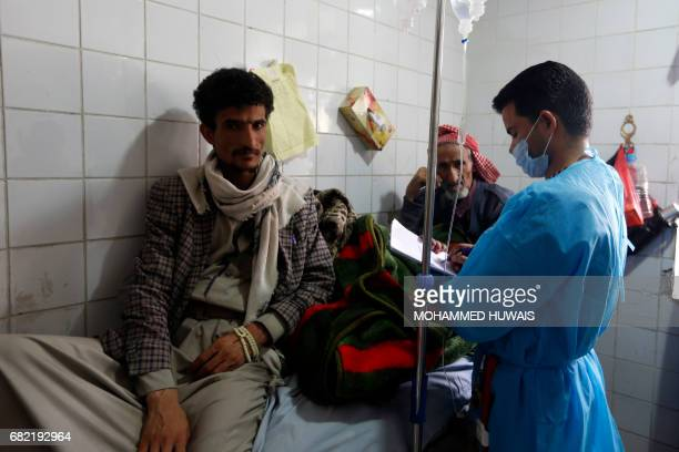 Yemeni men suspected of being infected with cholera receive treatment at a hospital in Sanaa on May 12 2017 / AFP PHOTO