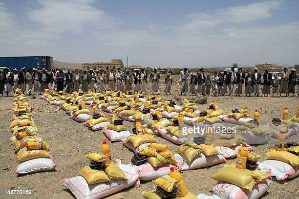 Yemeni men wait to collect food aid donated by a Kuwaiti charity laid out for internally displaced families living in a district of the Yemeni...