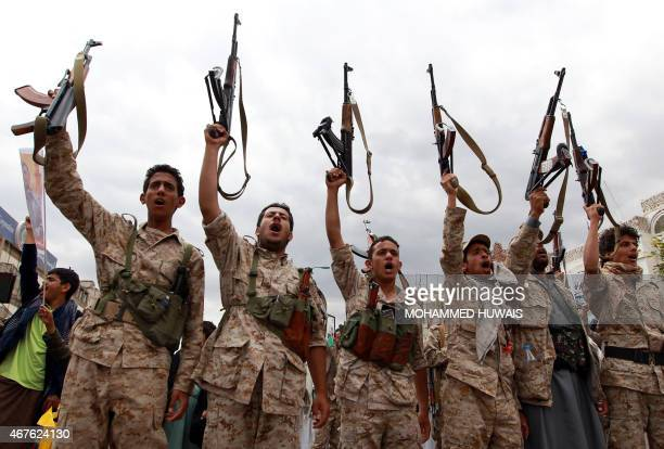 Yemeni men wearing military fatigue and loyal to the Huthi movement brandish their weapons on March 26 2015 during a gathering in Sanaa to show...