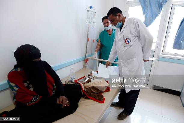 A Yemeni mother sits near her child suspected of being infected with cholera receiving treatment at a hospital in Sanaa on May 25 2017 Cholera has...