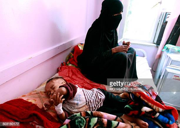 A Yemeni mother sits next to her malnourished infant at a therapeutic feeding centre in the capital Sanaa on January 2 2016 According to the UN...