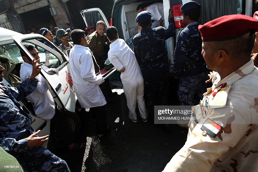 Yemeni paramedics carry the charred body of one of the victims into an ambulance at the scene where a military plane crashed in Sanaa on November 21, 2012, killing 10 people including the pilot, as it tried to make an emergency landing when an engine failed. The Antonov plane crashed in the Yemeni capital's northern neighbourhood of al-Hassaba while trying to land at an air base near Sanaa's main airport, according to the defence ministry and an airport source. AFP PHOTO/ MOHAMMED HUWAIS