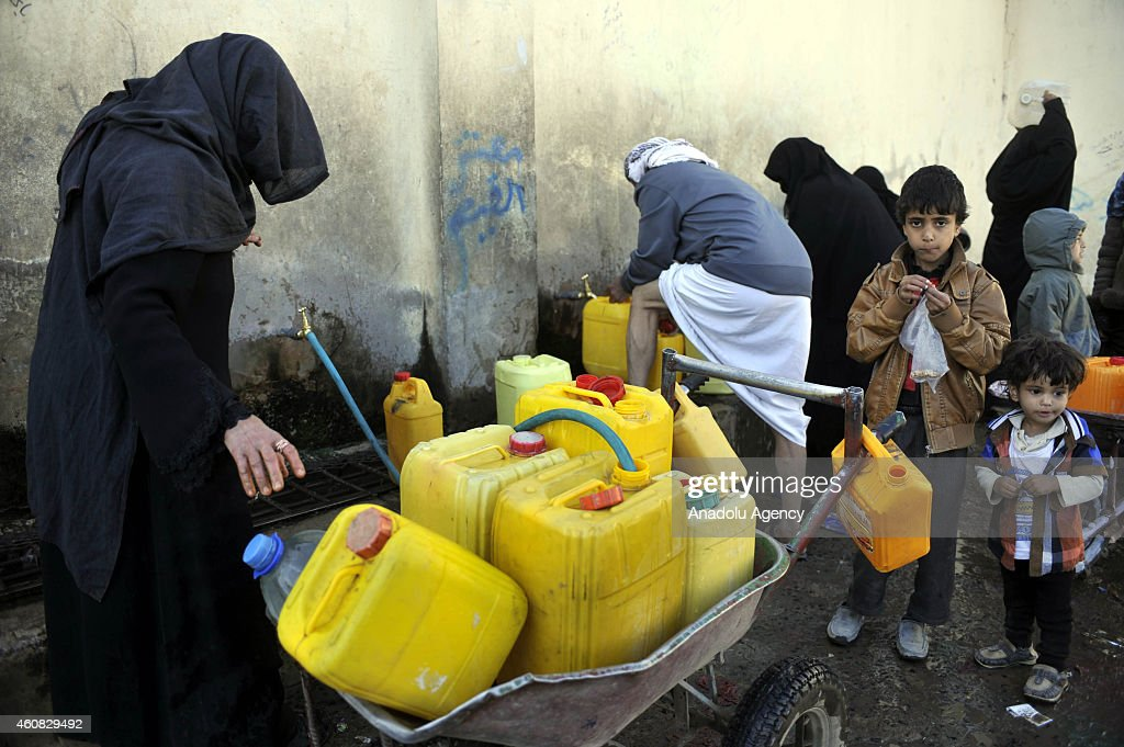 Yemeni people fill water inside containers from a public tap in al Madina area of Yemeni capital Sanaa on December 25, 2014. Sanaa faces water crisis as Yemen is one of the world's most water-stressed countries with the lack of access to clean water since the country is located in a dry and semi-arid region of the Arabian Peninsula in addition to not having the finances to develop and support the water desalination facilities.