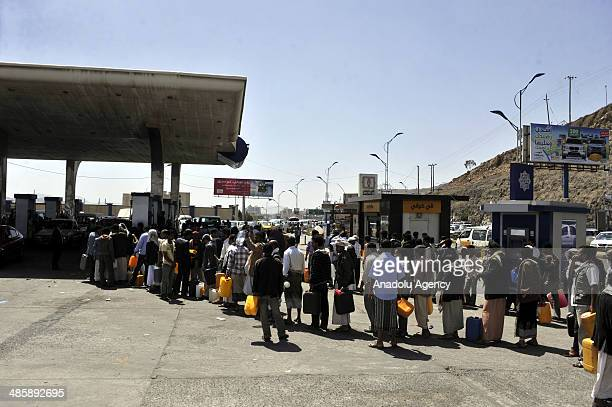 Yemeni people wait in queue to fill containers with petrol at a petrol station on April 21 2014 in Sanaa Yemen as the country sufferes from fuel...
