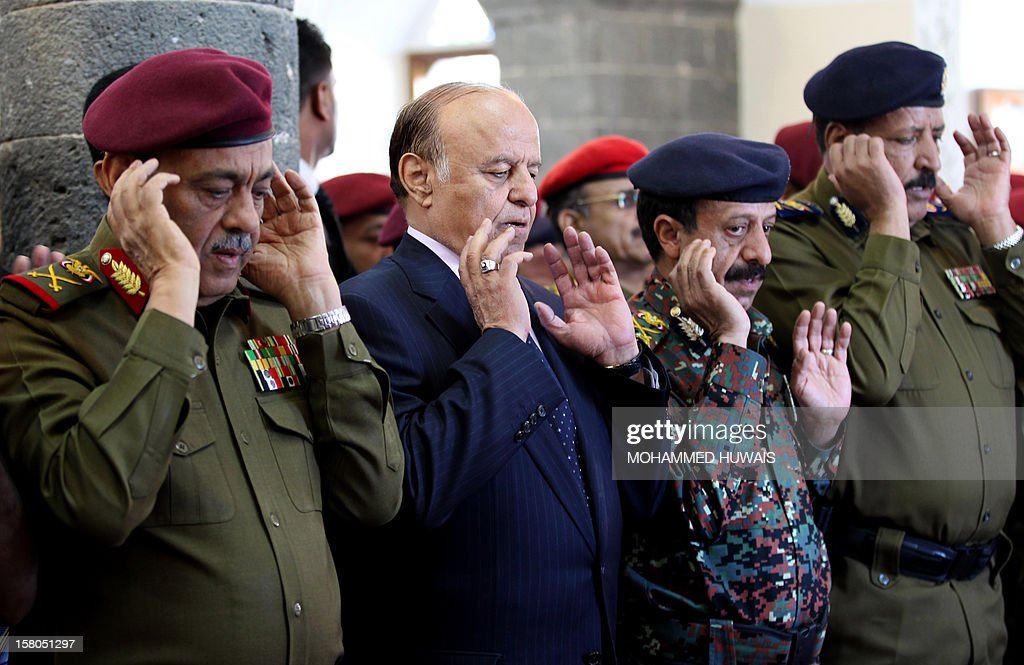 Yemeni President Abd Rabbo Mansour Hadi (2L) prays with military officers during the funeral procession in Sanaa on December 10, 2012, of military officers who were killed in an ambush on December 8. Four officers, including General Nasser Naji bin Farid, commander of military forces in central Yemen, were killed and six soldiers wounded in the attack by armed men, near Marib, 140 kilometres east of Sanaa, blamed on Al-Qaeda.