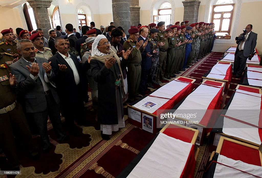 Yemeni President Abd Rabbo Mansour Hadi (C in blue suit) prays with military officers during the funeral procession in Sanaa on December 10, 2012, of military officers who were killed in an ambush on December 8. General Nasser Naji bin Farid, commander of military forces in central Yemen, was killed and six soldiers were wounded in the attack by armed men near Marib, 140 kilometres east of Sanaa, blamed on Al-Qaeda.