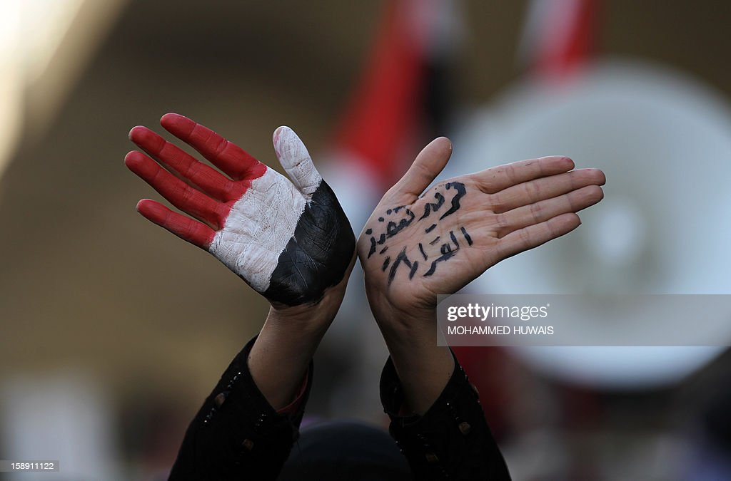 A Yemeni pro-democratic female protestor shows her hands painted in the colours of her national flag and text reading in Arabic: ' We want the implementation of the decisions' during a demonstration in Sanaa on January 3, 2013, demanding a quicker enforcement of President Abdrabuh Mansur Hadi's latest orders to restructure Yemen's military. AFP PHOTO/ MOHAMMED HUWAIS
