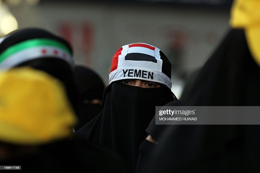 A Yemeni pro-demoncratic female protestor, wearing the niqab and a banner on her head bearing the colours of her national flag, attends a demonstration in Sanaa on January 3, 2013, demanding for a quicker implementation of President Abdrabuh Mansur Hadi's latest orders to restructure Yemen's military. AFP PHOTO/ MOHAMMED HUWAIS