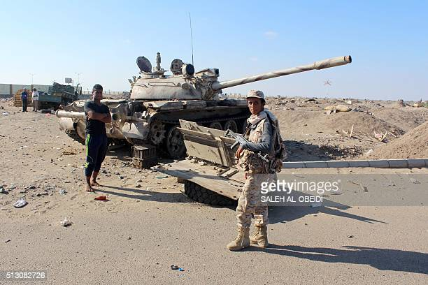 A Yemeni progovernment fighter stands near a tank at the site where a suicide bomber rammed his explosivesladen vehicle into an area where security...
