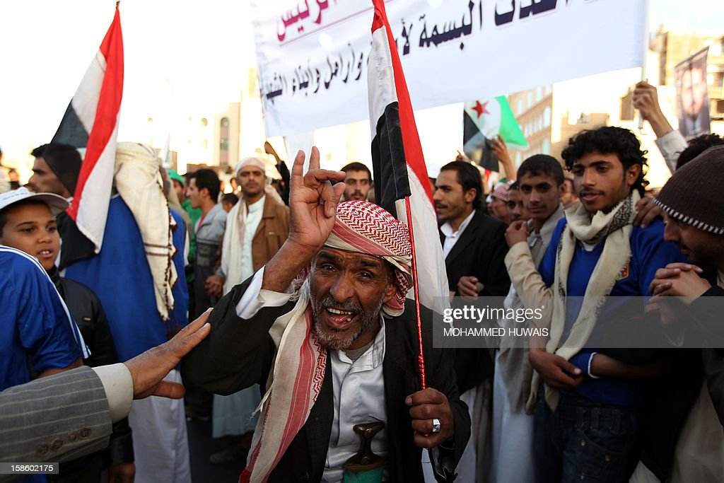 A Yemeni protestor gestures as he holds his national flag during a demonstration in Sanaa on December 20, 2012, in support of President Abdrabuh Mansur Hadi's decision to restructure Yemen's military. Hadi has dramatically restructured Yemen's military to curb the influence of those linked to toppled strongman Abdullah Ali Saleh with the strong backing of Yemen's Gulf neighbours.