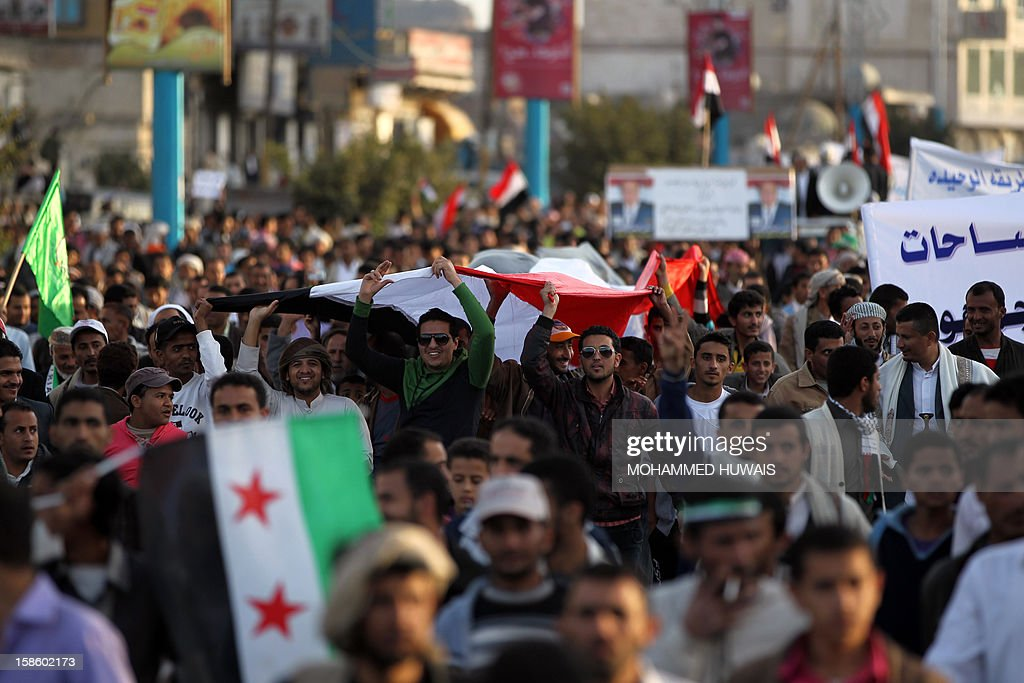 Yemeni protestors carry their national flag during a demonstration in Sanaa on December 20, 2012, in support of President Abdrabuh Mansur Hadi's decision to restructure Yemen's military. Hadi has dramatically restructured Yemen's military to curb the influence of those linked to toppled strongman Abdullah Ali Saleh with the strong backing of Yemen's Gulf neighbours.