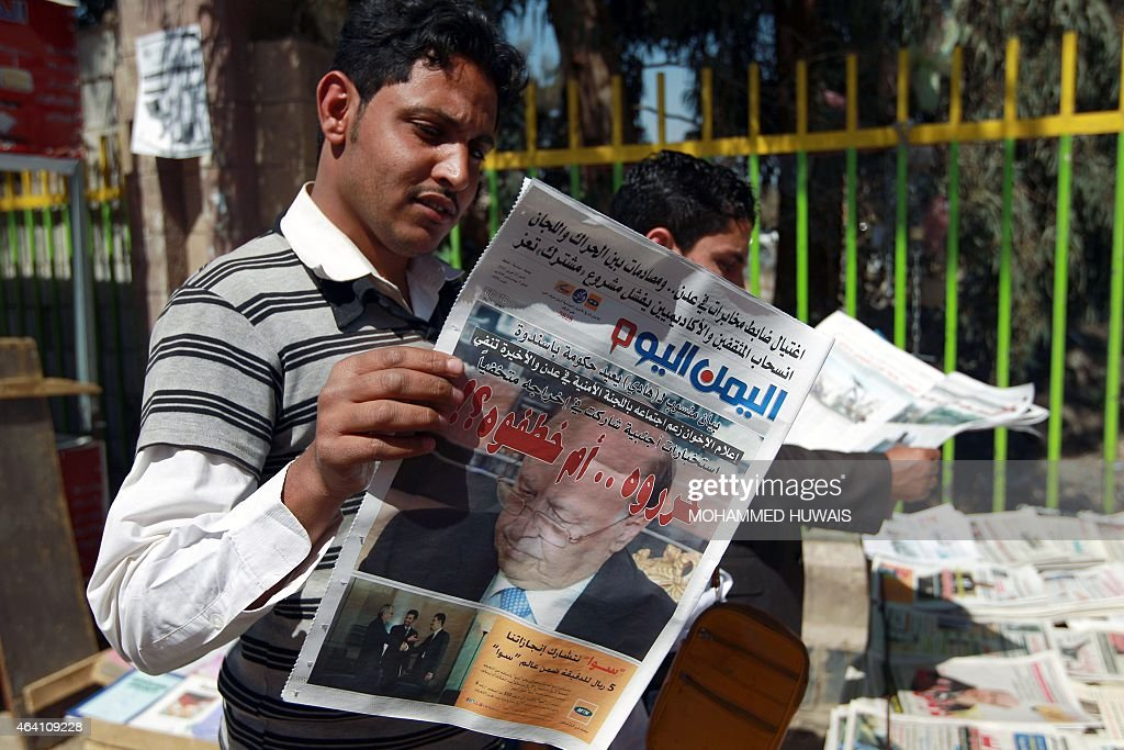 A Yemeni reads a local newspaper whose frontpage shows President Abedrabbo Mansour Hadi on February 22, 2015, in the capital Sanaa. Yemen's Western-backed president Hadi, who resigned last month under pressure from the Shiite Huthi militia, escaped house arrest and fled the capital to friendly territory on February 21, labelling as a coup the grab for power by the militia that had held him. AFP PHOTO / MOHAMMED HUWAIS