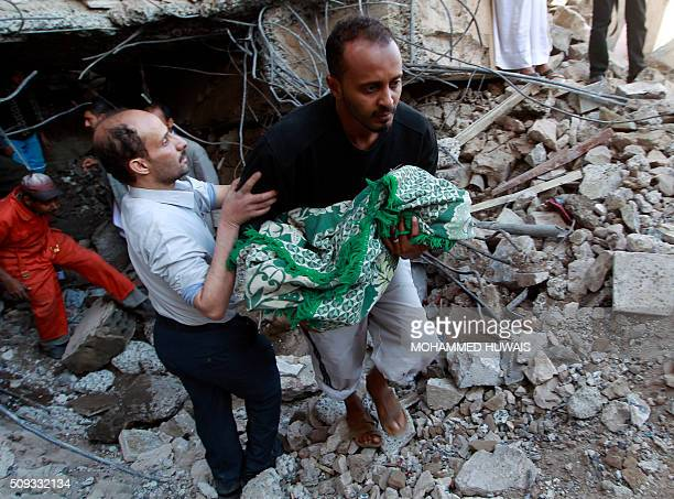 TOPSHOT Yemeni rescuers carry the body of a baby girl who was retrieved from the rubble of their home after the building was struck overnight by...