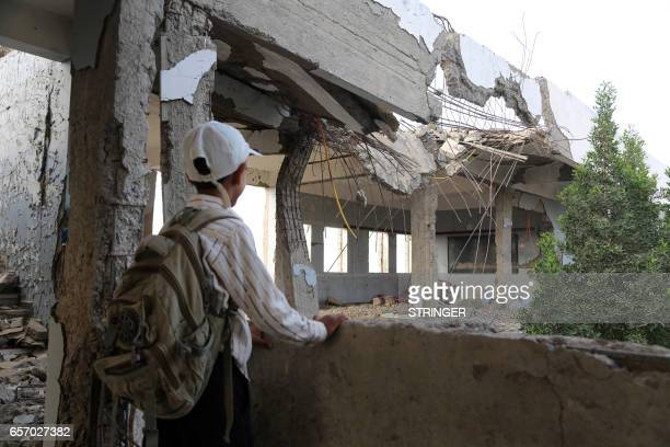 A Yemeni school boy looks at a destroyed school in the Yemeni port city of Hodeidah on March 15 which was damaged in the country's ongoing conflict...