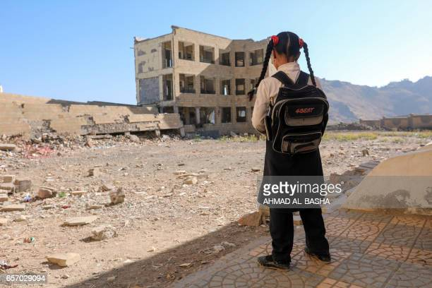 Yemeni school girl stands outside a school on March 16 that was damage in an air strike in the southern Yemeni city of Taez The conflict in Yemen...
