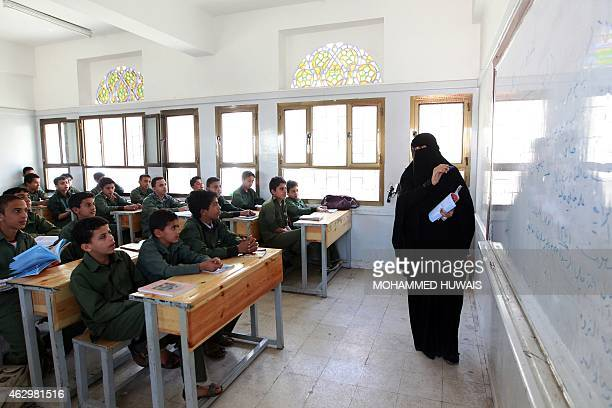 Yemeni schoolboys listen to a teacher during class in the capital Sanaa on February 8 two days after the Shiite Huthi militia seized power dissolving...