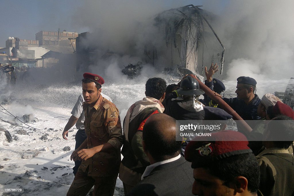 Yemeni security forces and firefighters rush to the scene of a military plane crash in Sanaa on November 21, 2012. Ten people including the pilot were killed as the Antonov jet tried to make an emergency landing when an engine failed, Yemen's defence ministry and an airport source said.