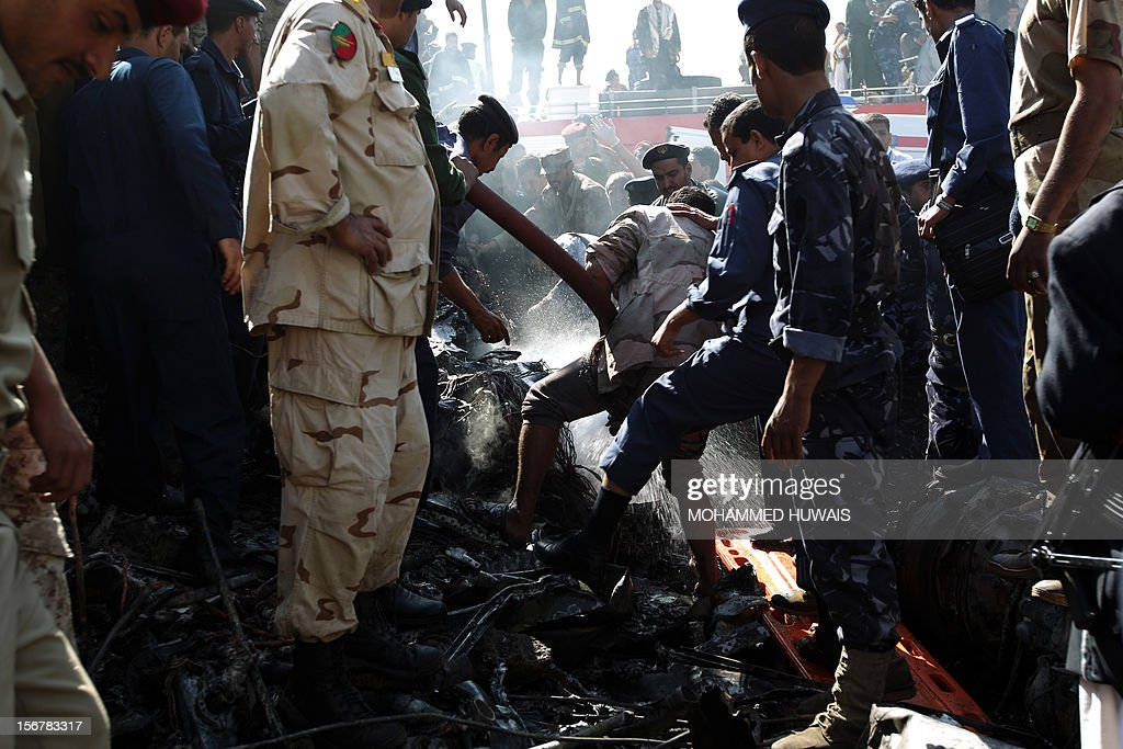 Yemeni security forces and firefighters work at the spot where a military plane crashed in Sanaa on November 21, 2012, killing 10 people including the pilot, as it tried to make an emergency landing when an engine failed, according to Yemen's defence ministry and an airport source. The Antonov plane crashed in the Yemeni capital's northern neighbourhood of al-Hassaba while trying to land at an air base near Sanaa's main airport.