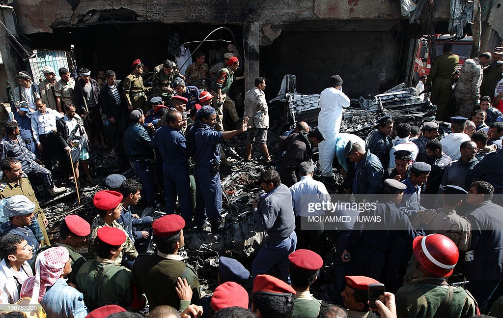 Yemeni security forces and rescue teams work at the scene where a military plane crashed in Sanaa on November 21, 2012, killing 10 people including the pilot, as it tried to make an emergency landing when an engine failed, according to Yemen's defence ministry and an airport source. The Antonov plane crashed in the Yemeni capital's northern neighbourhood of al-Hassaba while trying to land at an air base near Sanaa's main airport.